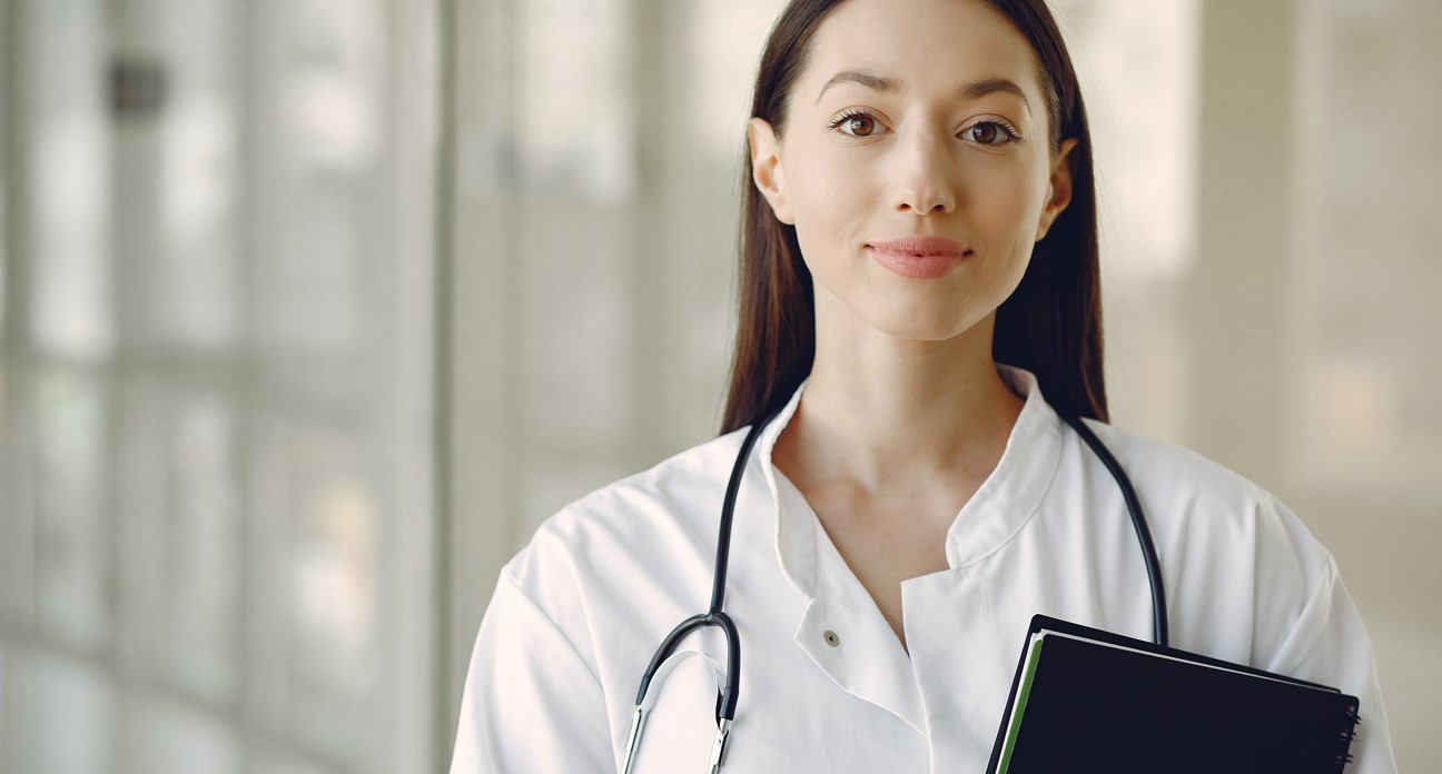Photo of a female doctor in a white coat holding a clipboard