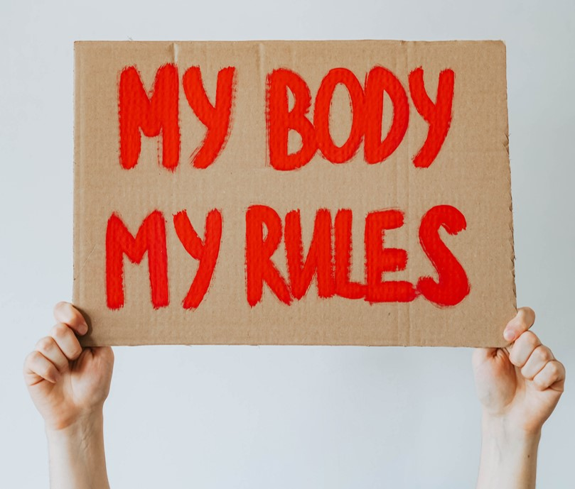 """Photo of a sign saying """"my body, my rules"""" in red paint"""