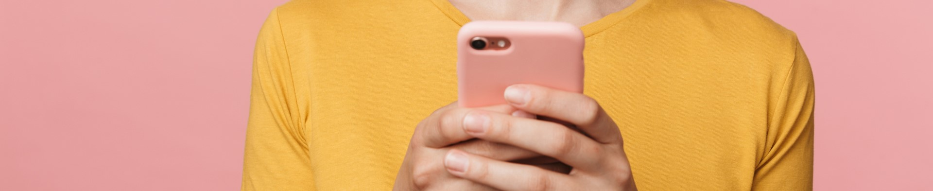Photo of hands holding a phone on a pink background
