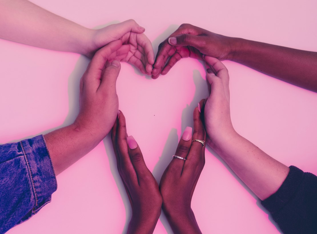 Photo of multiple hands shaped into a heart