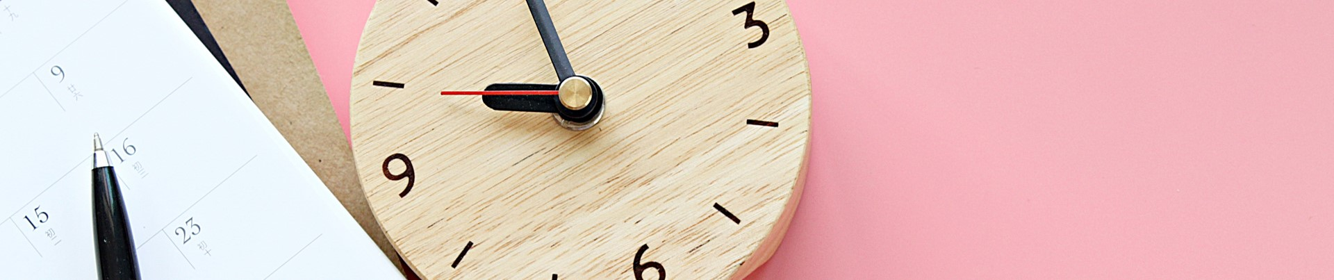 Photo of a calendar and wooden clock on a pink background