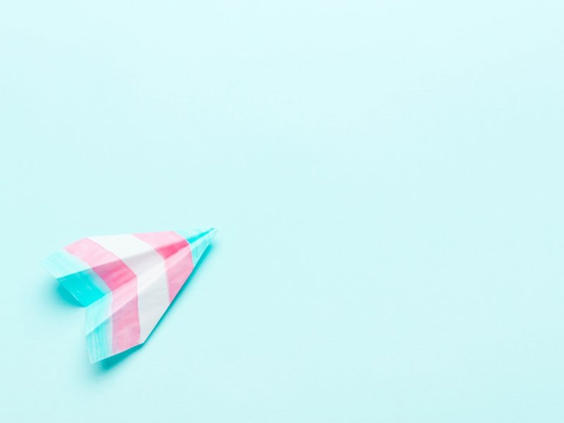 Photograph of a paper heart with the trans flag colours: pink, white and blue on a pale blue background