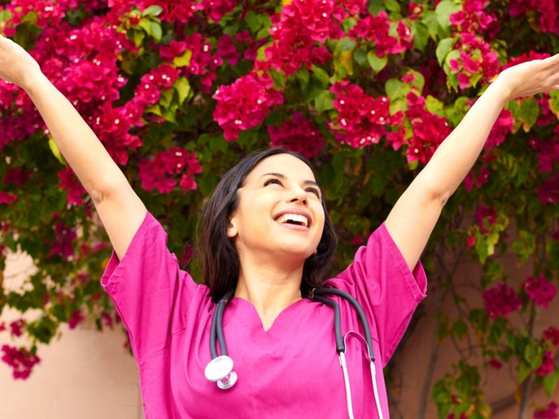 Photo of a woman in pink scrubs with her arms in the air, smiling