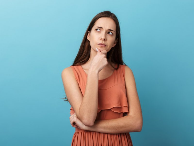 Photo of a woman in a thoughtful pose on a blue background